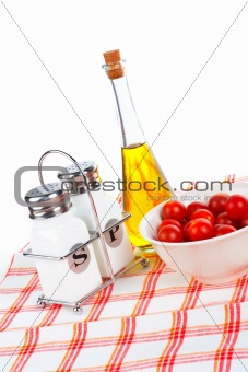 Oil bottle and tomatos cherry with salt and pepper