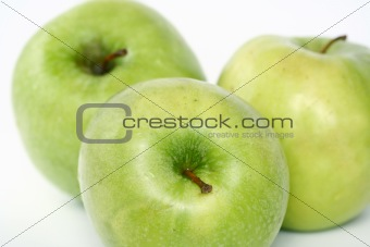 Three green apples in drops of water on a white background