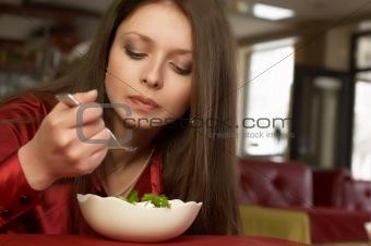 Beautiful brunette girl in red eats salad.