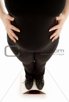 pregnant lady weighing oneself, focus on belly