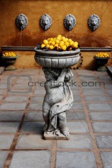 A statue of a boy holding lemons.