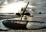 Red White Blue Dhow Sailing boat stranded at low tide in ocean M