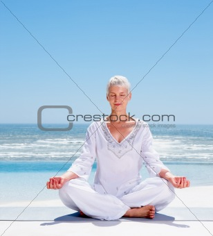 Mature woman meditating on the beach