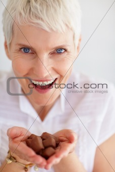 Closeup of cheerful mature woman eating chocolates