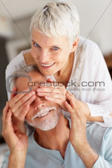 Smiling woman closing eyes of man