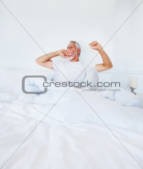 Old mature man lying on the bed and yawning