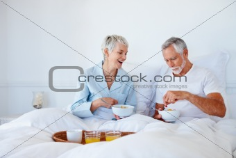 Aged couple enjoying a healthy breakfast in bed