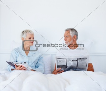 Retired couple in bed reading newspaper