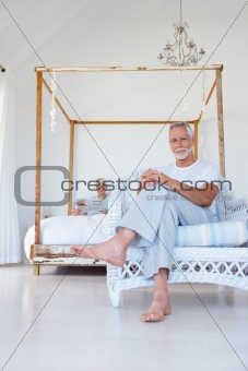 Senior old man relaxing on chair with wife at the back