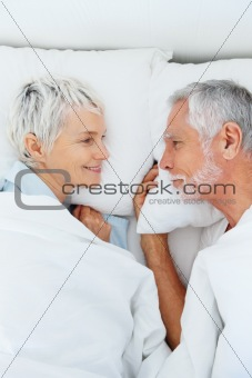 Happy senior couple having a good time in bed