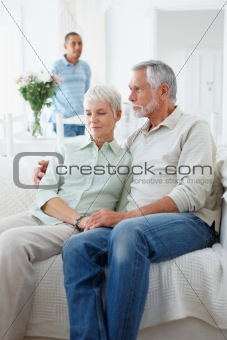 Old couple sitting together with man in background