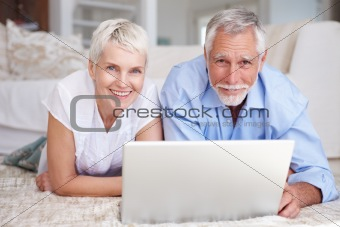 Old couple lying on floor and using laptop