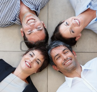 Portrait of a happy business group lying on floor
