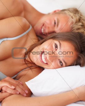 Smiling romantic young couple sleeping on bed