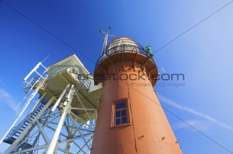 a red lighthouse at the beach in summer with a blue sky