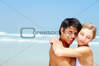 Romantic young couple hugging each other at the sea shore
