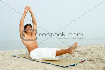 Handsome male doing yoga at beach