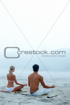 Young couple sitting at the beach in lotus position