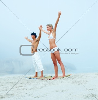 Young couple exercising at the beach