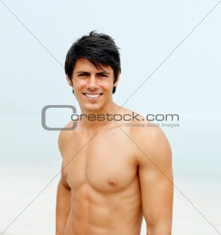 Handsome smiling young guy at beach