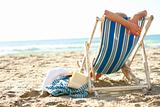 Rear view of a female on a deck chair at beach