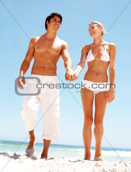 Young couple holding hands and walking on the beach