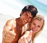 Young couple showing a gesture at the beach