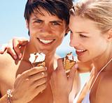 Closeup of a smiling young couple having ice cream