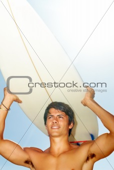 Strong young man lifting surf board on head