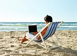 Man sitting on a deck chair using laptop at beach