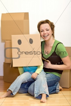 Little girl and woman having fun moving to a new home