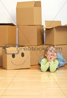 Little girl laying on the floor with lots of cardboard boxes