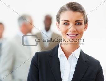 Portrait of young business woman with business people in background
