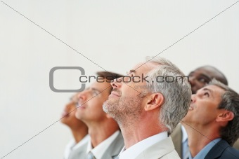 Business people looking upwards against isolated background