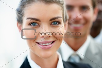 Closeup of confident young business woman with business people in background