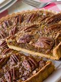 Pecan Pie With A Slice Being Cut