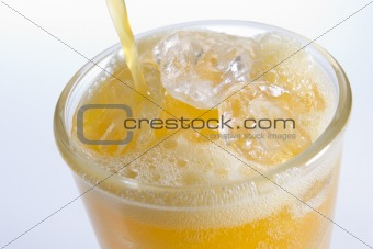 Pouring Orangeade Into A Glass Of Ice