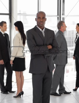 Business man looking at camera with group in background