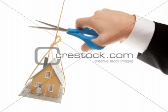 Hand with Scissors Cutting String Holding House Isolated on a White Background.