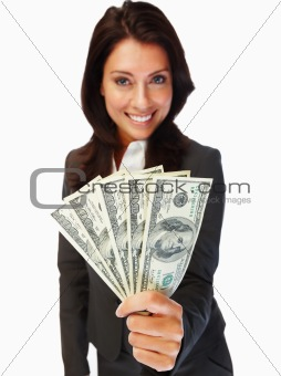 Smiling young business woman holding cash in front against isolated background