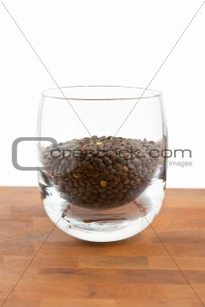 green lentils in glass on wooden table