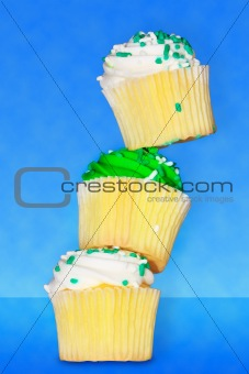 Three delicious vanilla cupcakes with buttercream frosting stack