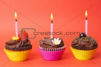 Miniature chocolate cupcakes with candles