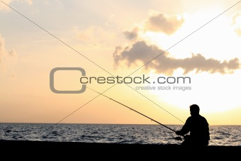 a man fishing at the sunset