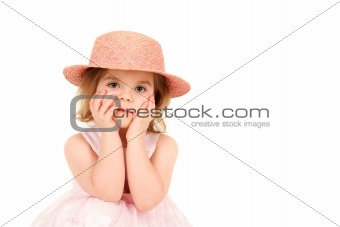 Portrait of young girl in pink princess dress and hat with hands on face, studio shot
