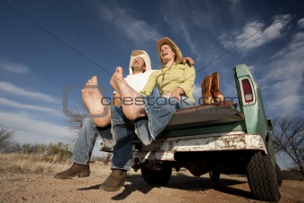 Cowboy and woman on pickup truck