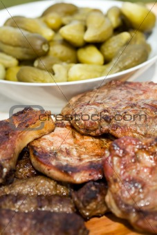 Grilled pork meat and pickled cucumbers
