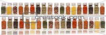 Assorted spices on two layer shelves against white