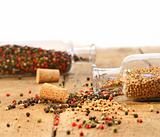 Peppercorns in glass bottles on wood table