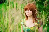 Portrait of a young beautiful woman with red hair in thick grass